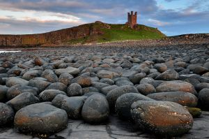 The late setting suns blasts Dunstanburgh Castle and the boulders